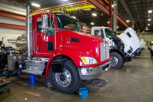 Red and white vacuum trucks being worked on and put together at FlowMark in Kansas City
